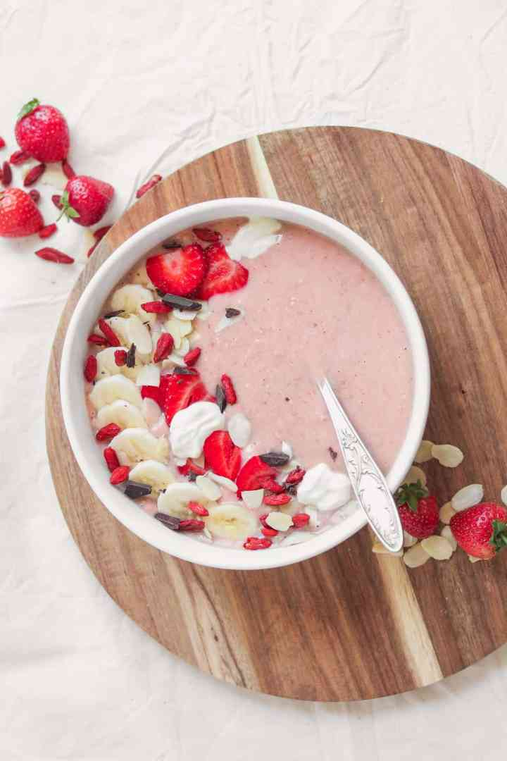 Vegan strawberry smoothie in a white bowl resting on a table with nuts and berries in the background