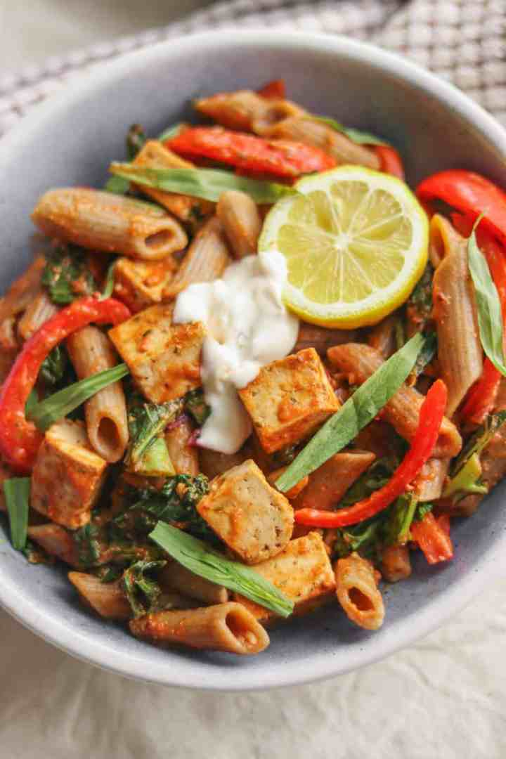 Bowl of creamy vegan tomato sauce pasta with tofu and red peppers