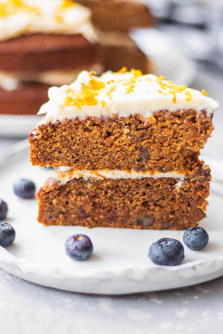 Slice of vegan carrot cake on a white plate with frosting