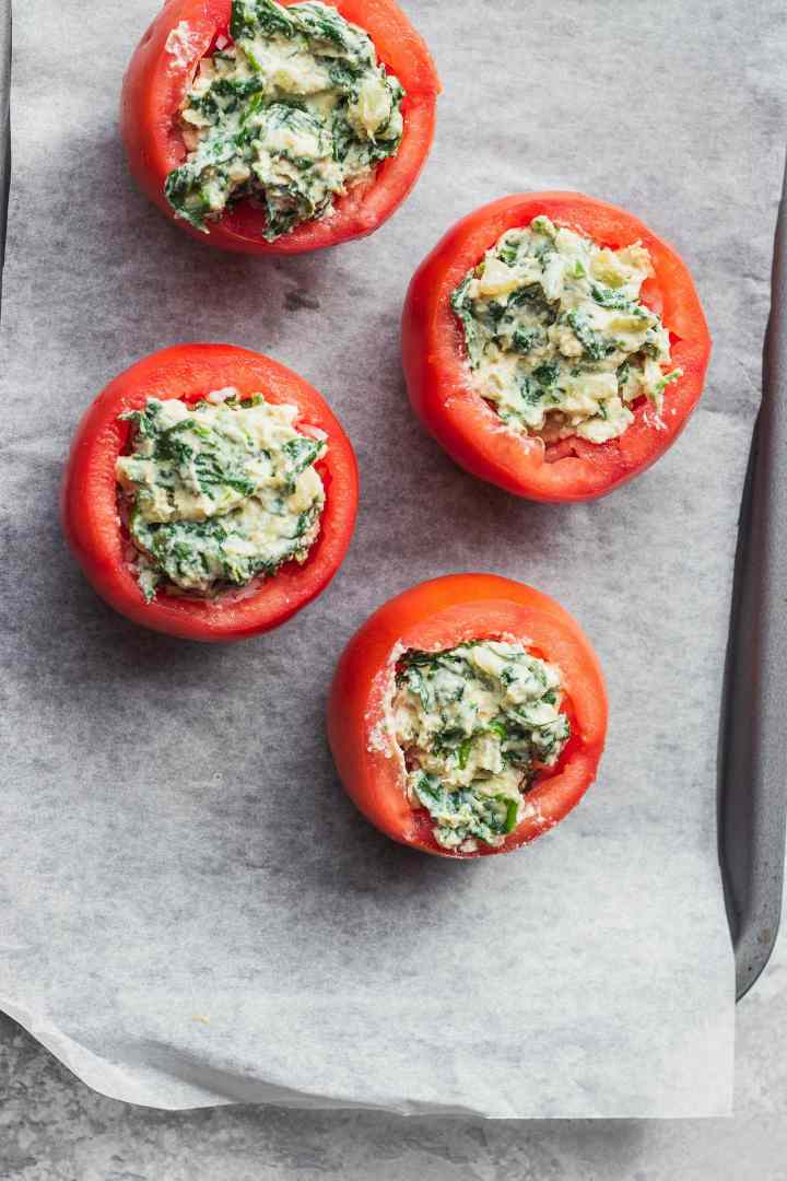 Stuffed tomatoes with rice and creamed spinach on a baking tray