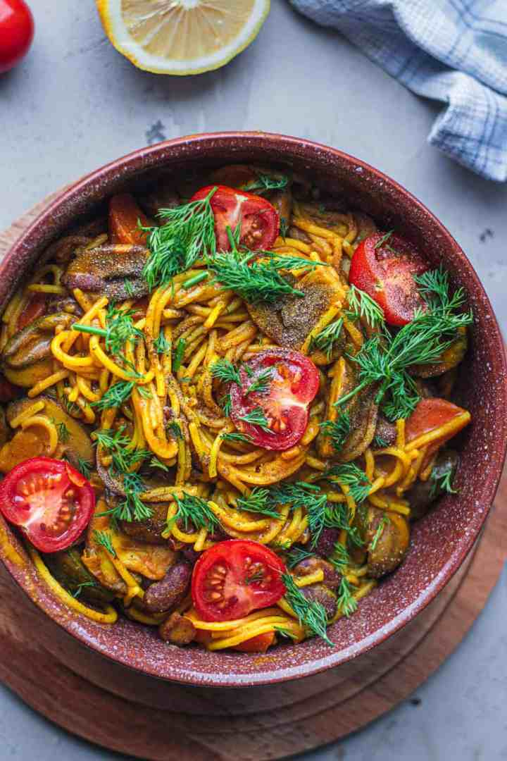 Spaghetti with beans and vegetables in a brown bowl