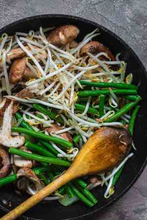 Mushrooms beansprouts and green beans in a frying pan