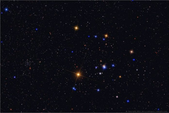 Spread-out cluster of bright multicolored stars, the 5 brightest arranged in a sideways V.