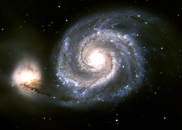 Spiral galaxy shown as bright central light and surrounding spiral arms, with a companion irregular (bright light) galaxy on the left side.