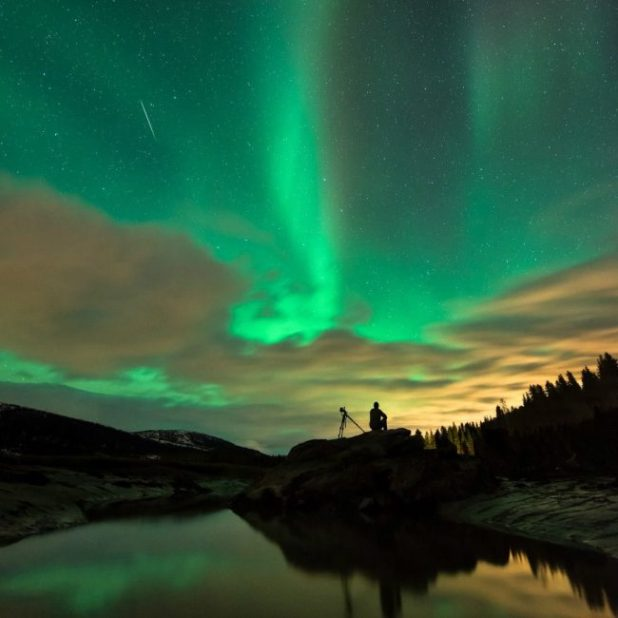 A camera My silhouetted man with a tripod sees a thin line in the sky in front of a huge, swirling green aurora.