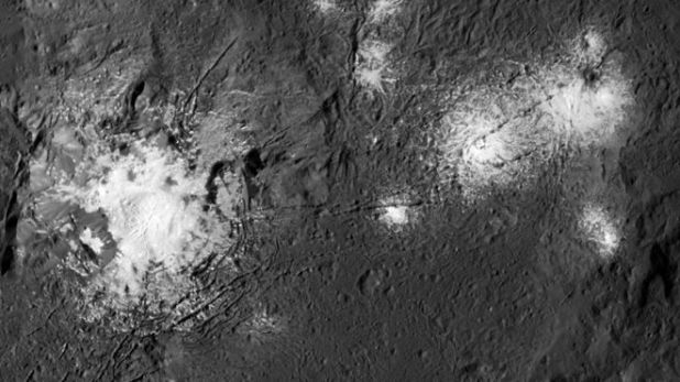 Large and small bright white patches on a gray pit surface.