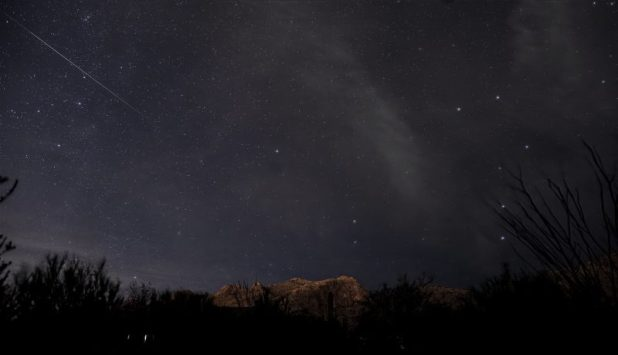 In the dark sky in tall thin bright length, with large dipper visible.