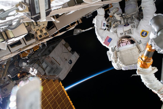Upside-down astronaut in white space suit with American flag patch outside space station.