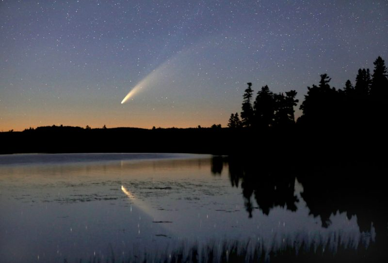 Comet in the sky above a lake, also reflecting in the lake.