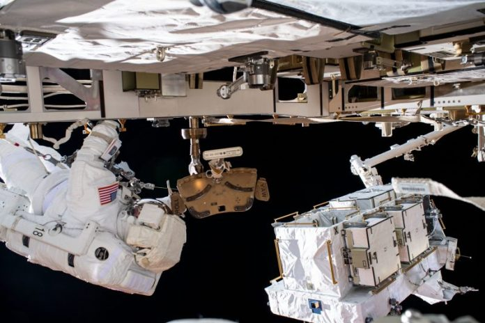 Astronaut in spacesuit outside spacecraft with white-covered box at end of jointed arm.