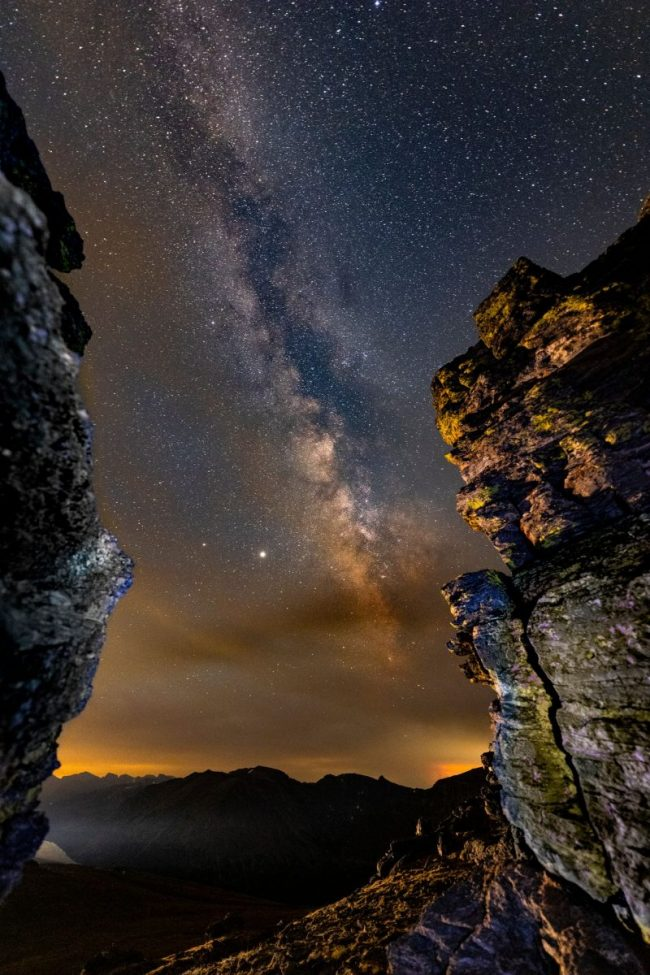 Edgewise view of the summer Milky Way in starry sky, on a dark night, between 2 rock cliffs.