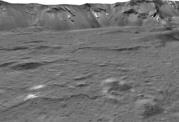 A somewhat lumpy pit floor with a steep crater wall in the distance.