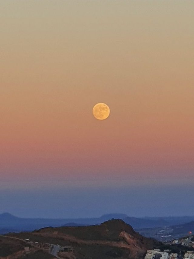 Yellow moon floating in pink sunset sky over blue hills.