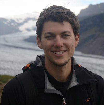 A smiling man with a glacier behind him.