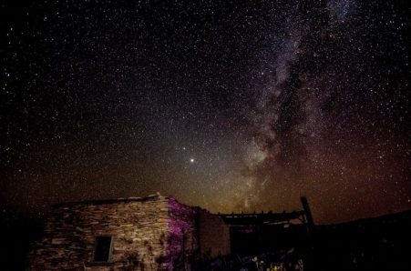 Campo de estrelas muito denso e pano de fundo da Via Láctea para Júpiter e Saturno, acima de um edifício de pedra abandonado.