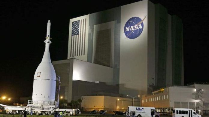 Night view of stocky white rocket near gigantic building with flag and NASA logo on it.