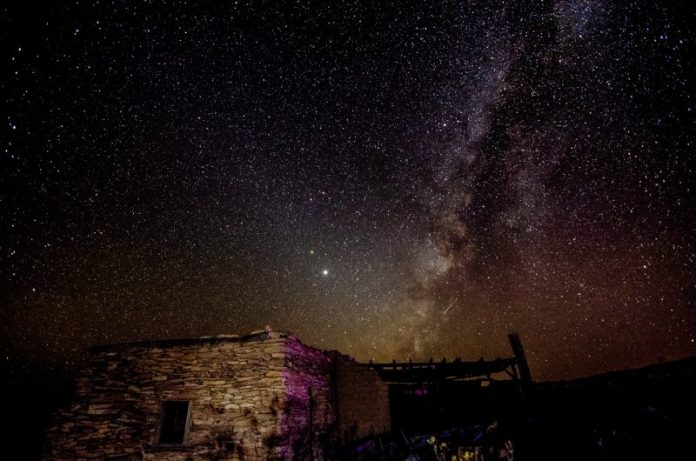 Jupiter, Saturn, Milky Way, above an abandoned stone building, under a dark desert night sky.