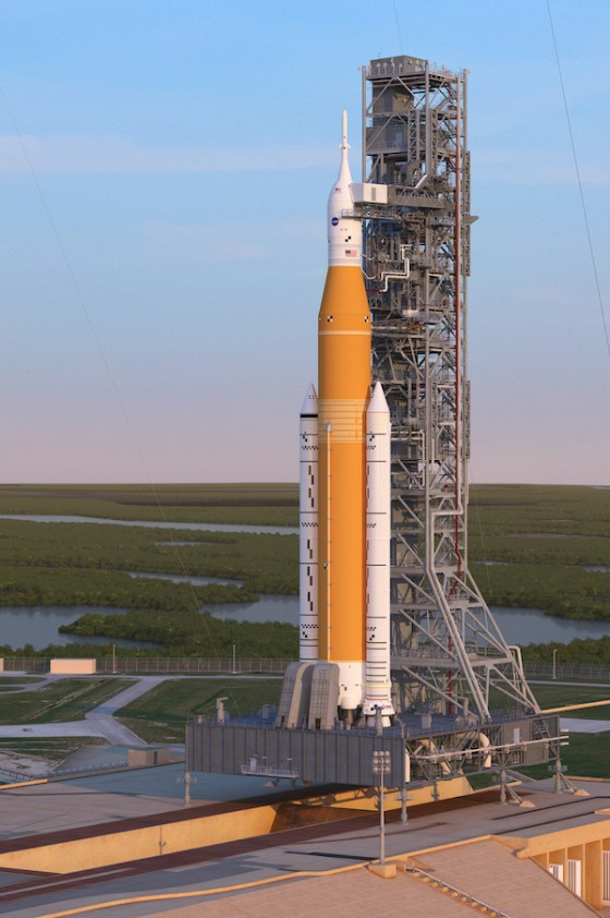 High orange rocket with 2 side accelerators standing next to a launch tower.