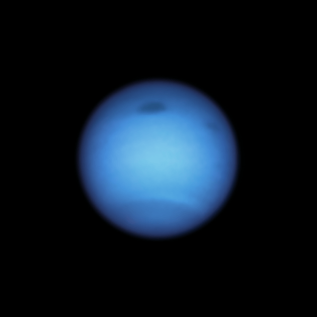 Large bluish planet with two dark spots and bands in the atmosphere.