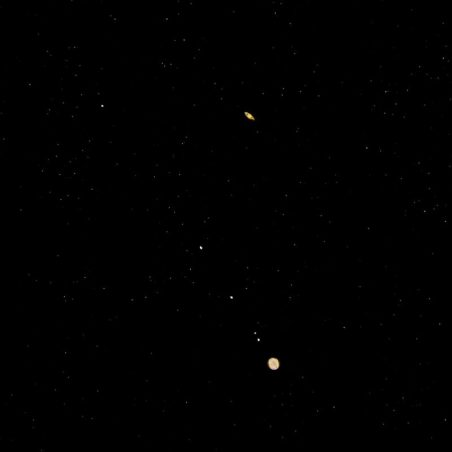 Saturn, with rings, above Jupiter, with moons. Both planets tiny.