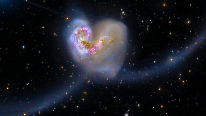 Two galaxies swirling together in a heart shape.