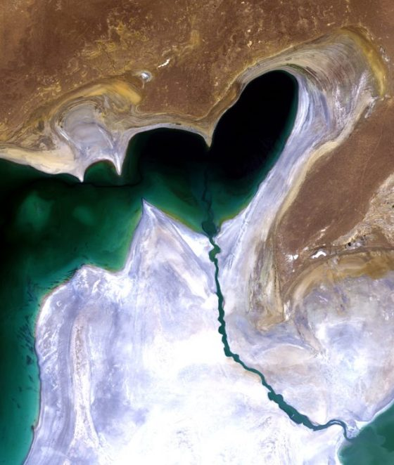 Dark green heart-shaped lake on brown and white ground.