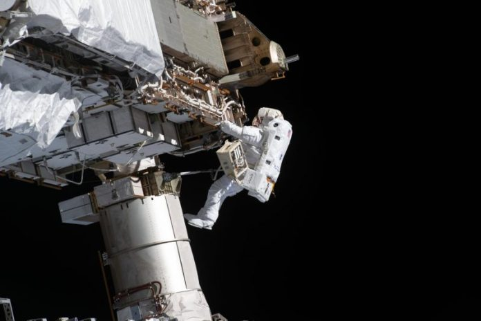Astronaut in a white spacesuit against background of ISS.