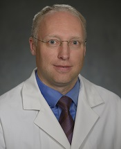 A man with gray hair and glasses in a white lab coat.