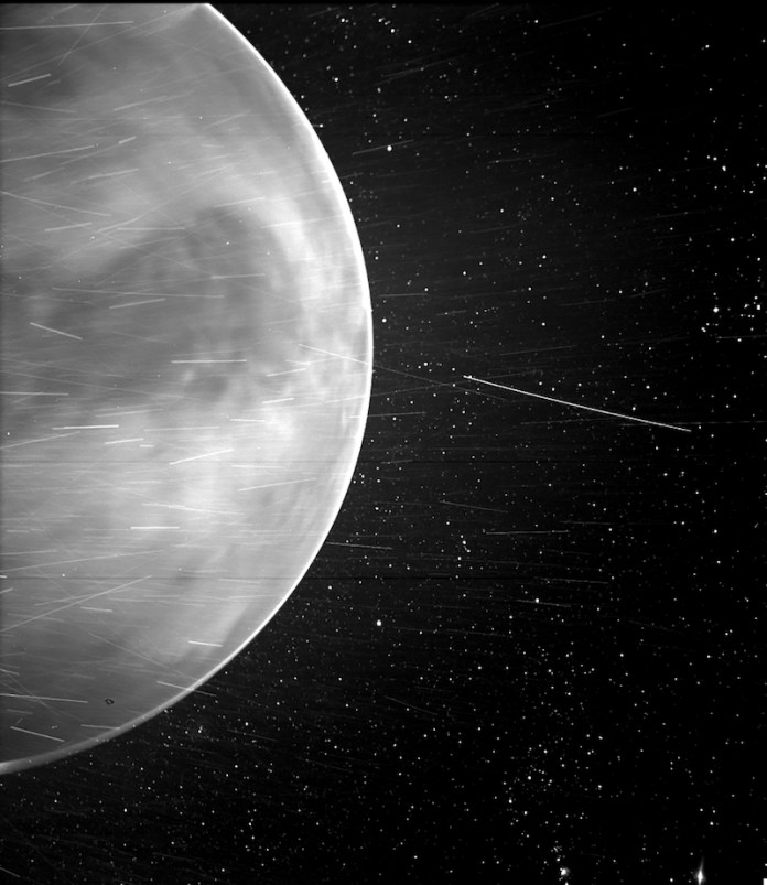Planet in black and white with many thin streaks around it and stars in the background.