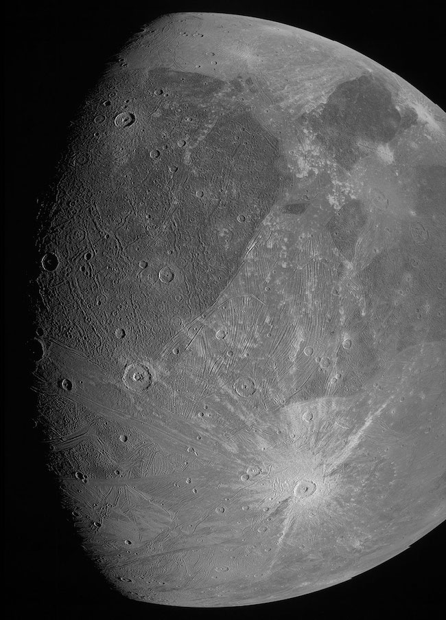 Moon-like body with craters, bright and dark patches, and lines.