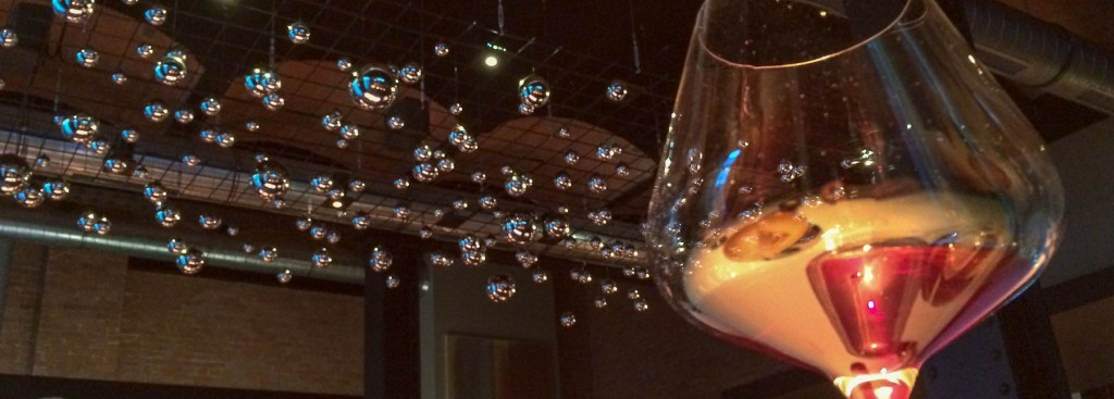View of ceiling through a wine glass at the Berlin restaurant Reinstoff.