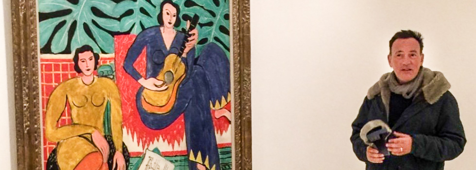 Picture of Bruce Springsteen standing next to a Matisse painting.