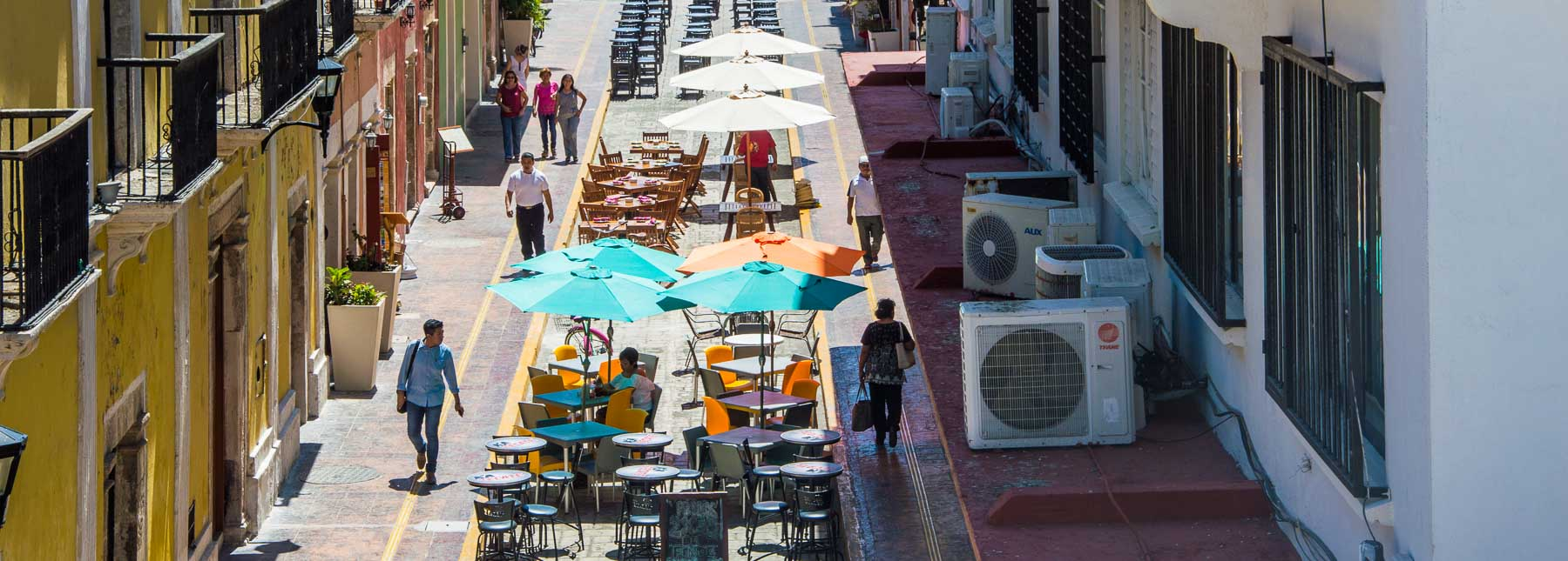 Tables shaded by umbrellas on a Campeche street.