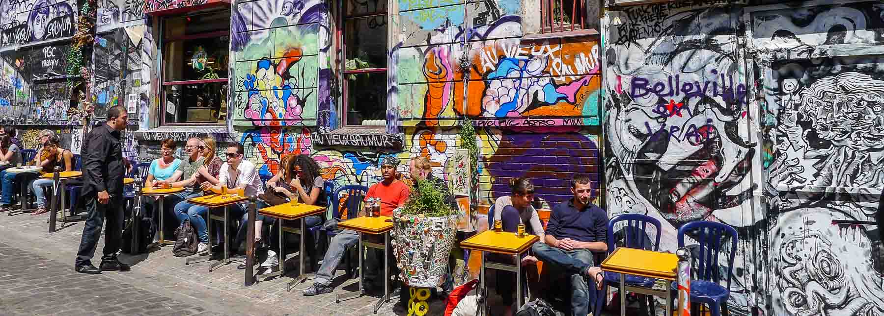 People sitting at tables in front of painted wall.