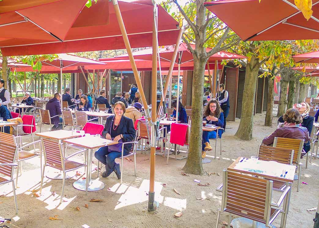 People sitting under umbrellas in outside café.