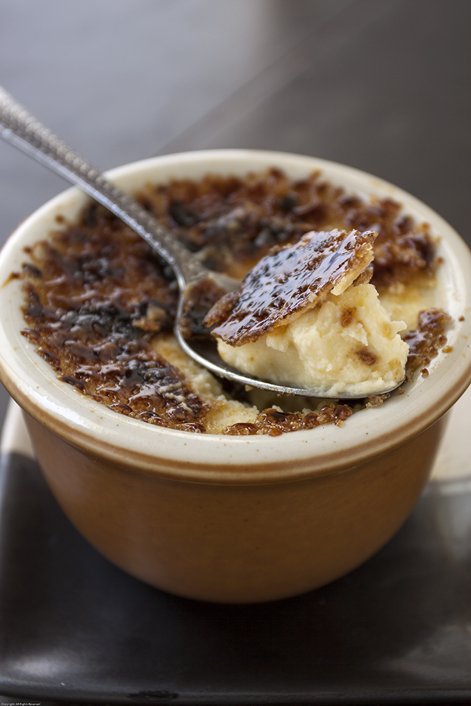 Crème Brûlée with spoonful of custard lifted