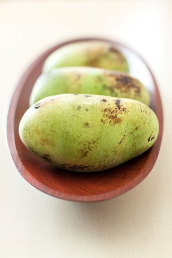 Pawpaws ripening in a wooden bowl