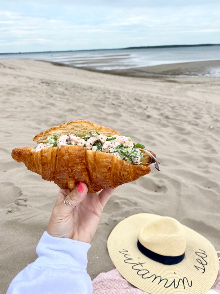 Crystal Richard of East Coast Mermaid holding a fresh cold water shrimp roll on the beach in New Brunswick