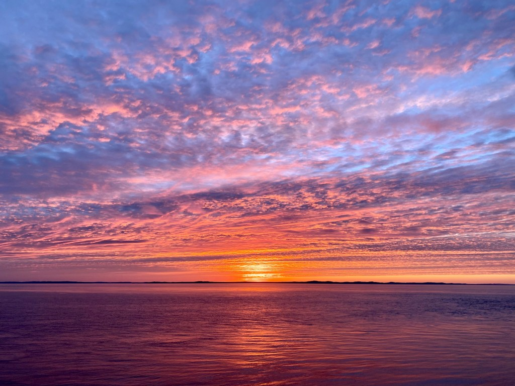 A stunning blue, purple, pink and orange sunset in Grand Manan over the water.