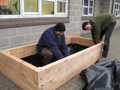 Jim and Jack build the raised bed at school with a liner to retain the topsoil