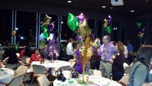 EMBA members at the Mardi Gras Banquet wearing beads and festive decor on the tables