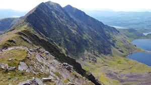 View of the three main summits of Caher from the side of Carrauntoohil. The north side is very steep bare rock. The grassy south side slopes more gently.