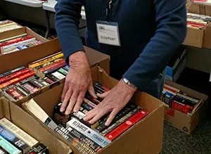 volunteer with a box of donated books