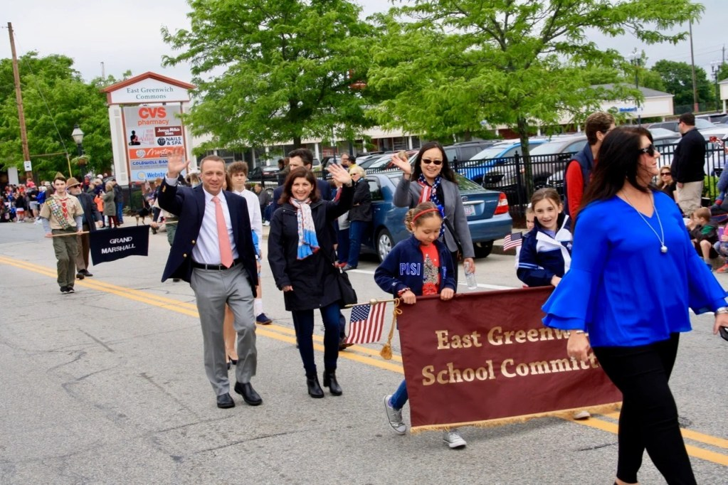 School Committee members, from left, Michael Fain, Chairwoman Carolyn Mark, and Yan Sun wave to parade viewers.