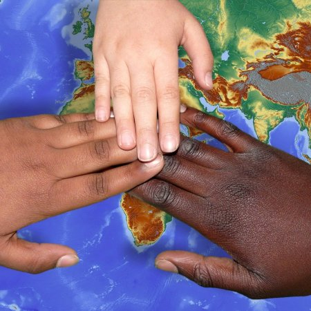 Three hands joined together over a map of the world
