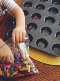 Buddy filling the muffin tin with broken crayons