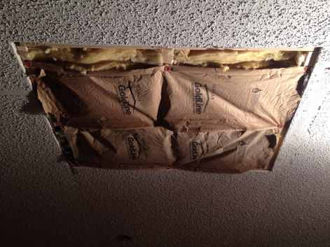 A hole in the ceiling with insulation stuffed in it.