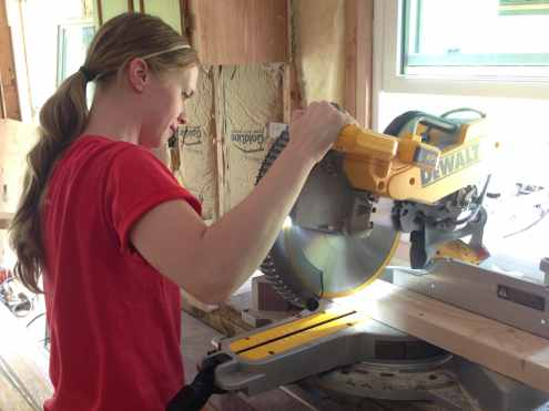 Jenn cutting lumber for a homestead project