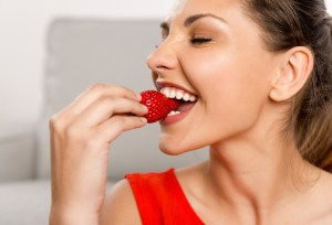woman at home eating strawberries