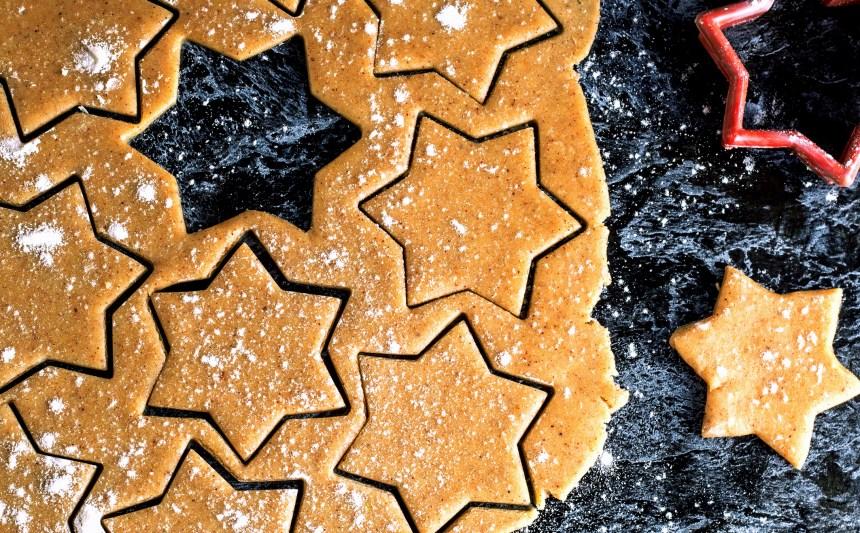 Weihnachtlicher Plätchenteig in Sternform ausgestochen auf dunklem Hintergrund